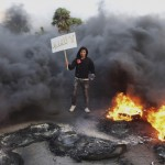 A man holds a sign amid smoke and fire after angry protesters set tyres on fire in a street during a demonstration against the General National Congress in Benghazi